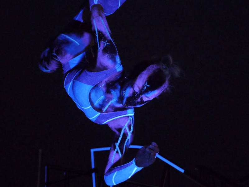 Aerialist in UV painted as the Universe